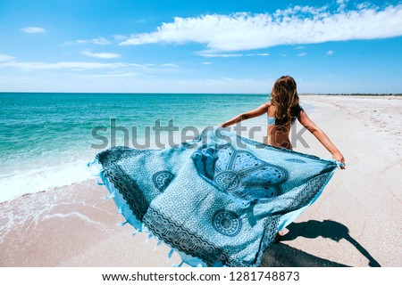 Girl relaxing on the beach, looking at sea landscape and holding boho pareo on the wind