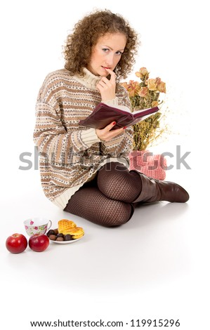 girl relaxing with a book with a cup of tea and food - stock photo