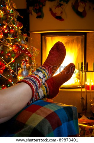 girl resting in a room with a burning fireplace and Christmas tree