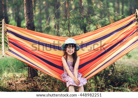 Girl resting on a hammock in forest.