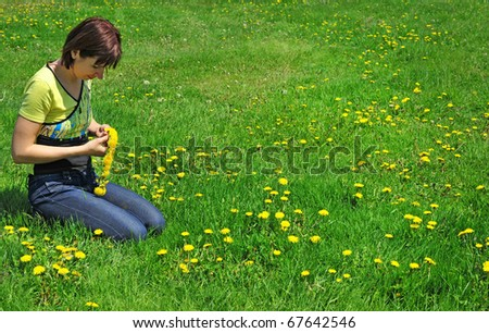 girl resting on the green meadow with   dandelion flowers