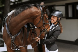 Girl rider adjusts saddle on her horse to take part in horse races.