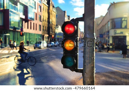 Girl rides on the street on a bicycle among the cars in the city center in a beautiful light by a traffic light with red and orange