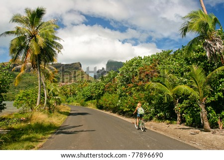 Girl riding a bicycle through the tropical  island Bora Bora , French Polynesia - stock photo