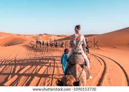 Girl riding a camel in Sahara Desert Morocco. Camel expedition in the desert.