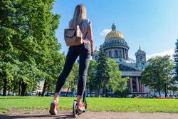 Girl riding a scooter in Saint Petersburg. Leggy girl admires St. Isaac Cathedral. Riding a scooter on St. Isaac square. Summer in Petersburg. Sights Of Russia.
