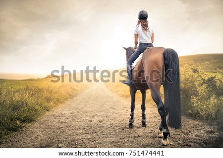 Girl riding her horse in a path in the hills #751474441
