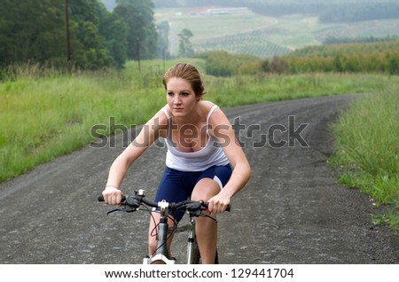 Girl riding mountain bike through forest