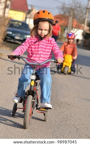 girl riding on his first bike in a helmet