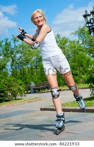 Girl roller-skating in the park at summer