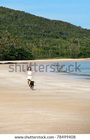 girl running along the beach  playing with dog