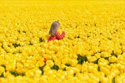 Girl running in a yellow tulip field