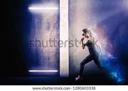 Girl running next to the grungy wall with neon lights. Photo is stylized to add a sense of energy and endurance. Endurance and energy concept.