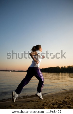 Girl running on a beach - stock photo