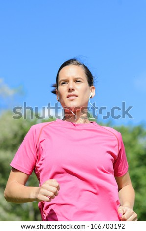 Girl running on sunny summer on park. Young caucasian female athlete exercising.