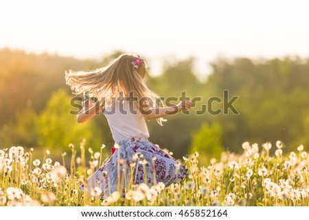 Stock Photo Girl running on the field of dandelions on sunset. Beautiful little kid dancing on dandelion meadow. Summer fun outdoors.