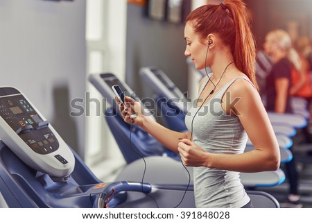 Girl running on the treadmill and listening to music at the gym, soft focus picture