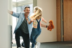Girl running towards her father at the entrance door holding a teddy bear. Daughter meeting her father just arrived from a business trip.