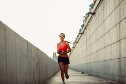 Girl runs along the concrete wall at sunset, wearing heart rate monitor