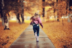 Girl 6-7 runs in the autumn park