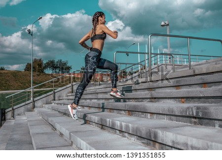 Girl runs in the summer in the city, on the morning run. Stair background, blue sky with clouds. Clothing leggings top. Free space for text. Phone earphones.