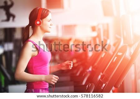 Girl runs on treadmill. Active girl in gym runs on treadmill. Athlete cardio activity on treadmill.