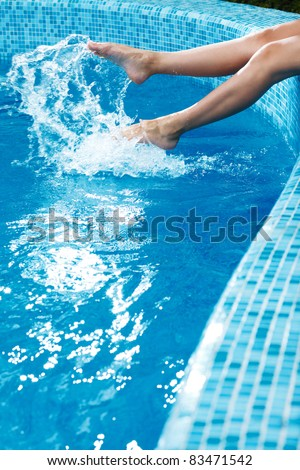 girl's beauty legs in the pool making splashes