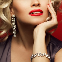 Girl's best friends and femme fatale concept. Marilyn Monroe style. Close up portrait of rich woman smiling wearing expensive luxurious diamond bracelet, earring. Studio shot