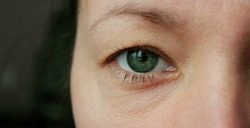 Girl's eye close-up. Macro image of a human green eye. Beautiful discerning look of female eyes without makeup. Close up shot