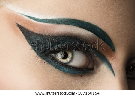 girl's eye closeup with creative green makeup, it looks at right