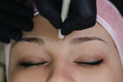 Girl's face with closed eyes close-up. The master in black gloves holds a white pencil and draws auxiliary lines between the eyebrows for permanent makeup.