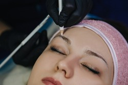 Girl's face with closed eyes close-up. The master in black gloves holds a white pencil and draws an eyebrow shape for permanent makeup