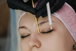 Girl's face with closed eyes close-up. The master in black gloves with a yellow stylus measures the beginning of the eyebrow to mark the sketch for microblading with a white pencil.