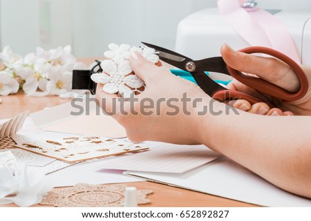 Girl's hand cut paper, scrapbooking for wedding or other festive decorations . Tools for scrapbooking.
