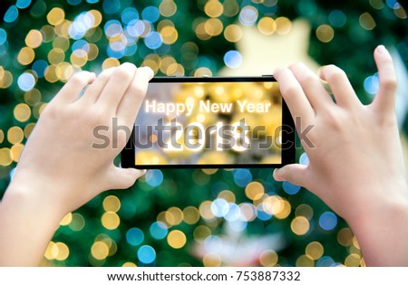 Girl's hand holding mobile phone take a photo of christmas tree with wording Happy New Year 2018. Young woman using smartphone outdoor capture picture of bokeh blur Christmas lighting lamp decoration.