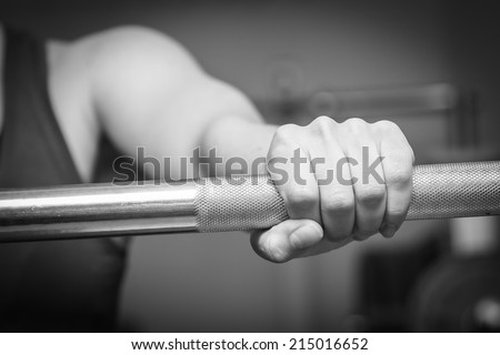 Girl\'s hand on the barbell. Beautiful girl goes in for sports in the gym. Girl holding a barbell. Gym, strength, fitness - Healthy lifestyle concept. Article about women\'s fitness.