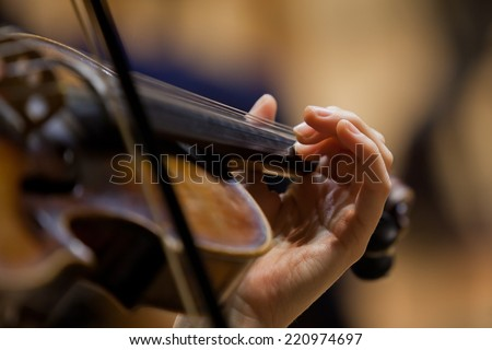 Girl's hand on the strings of a violin
