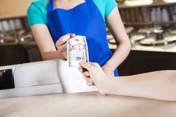 Girl's Hand Paying Money To Worker In Ice Cream Parlor