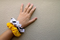 Girl's hand showing two textile scrunchies, hair elastic used as a fashion accessory. Wall textured background.