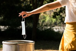 Girl's hand throwing Medical face mask in the paper bin in a park. single use face mask. Right way to throwing used face mask in bin. Coronavirus or Covid-19 concept.