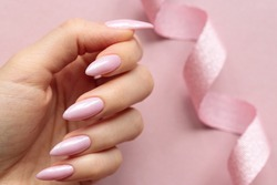 Girl`s hand with a beautiful long nails covered by light pink polish on a pink background with ribbon