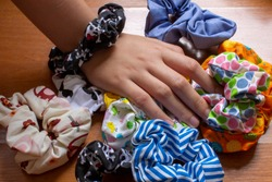Girl's hand with textile scrunchies, hair elastic used as a fashion accessory.