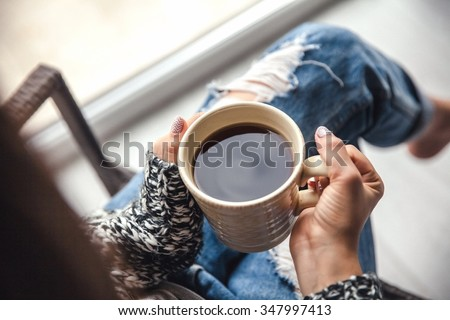 Girl\'s hands holding a cup of coffee, ripped jeans. Fashion manicur