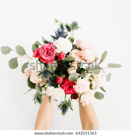 Girl's hands holding beautiful flowers bouquet: bombastic roses, blue eringium, eucalyptus, isolated on white background. Flat lay, top view. Floral composition #642031363