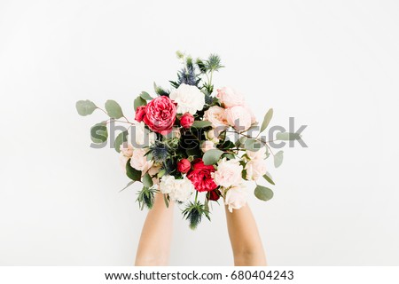 Girl's hands holding beautiful flowers bouquet: bombastic roses, blue eringium, eucalyptus, isolated on white background. Flat lay, top view. Floral composition