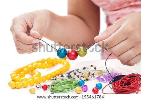 Girl's hands making a necklace with wooden beads