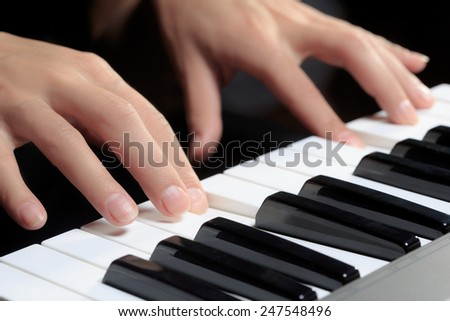 Girl\'s hands on the keyboard of the piano