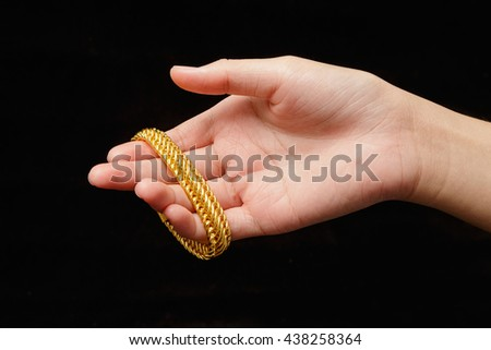 Girl's hands with golden bracelets on black background