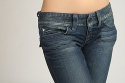 Girl's hips in jeans close-up. Woman in denim pants close up. She has a bare belly. Hips of a slender girl in denim trousers. Fashion clothing femininity concept. Casual wear for women.