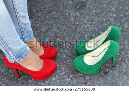 Girl\'s legs on the pavement in red high heels and green shoes heels one choice Filling